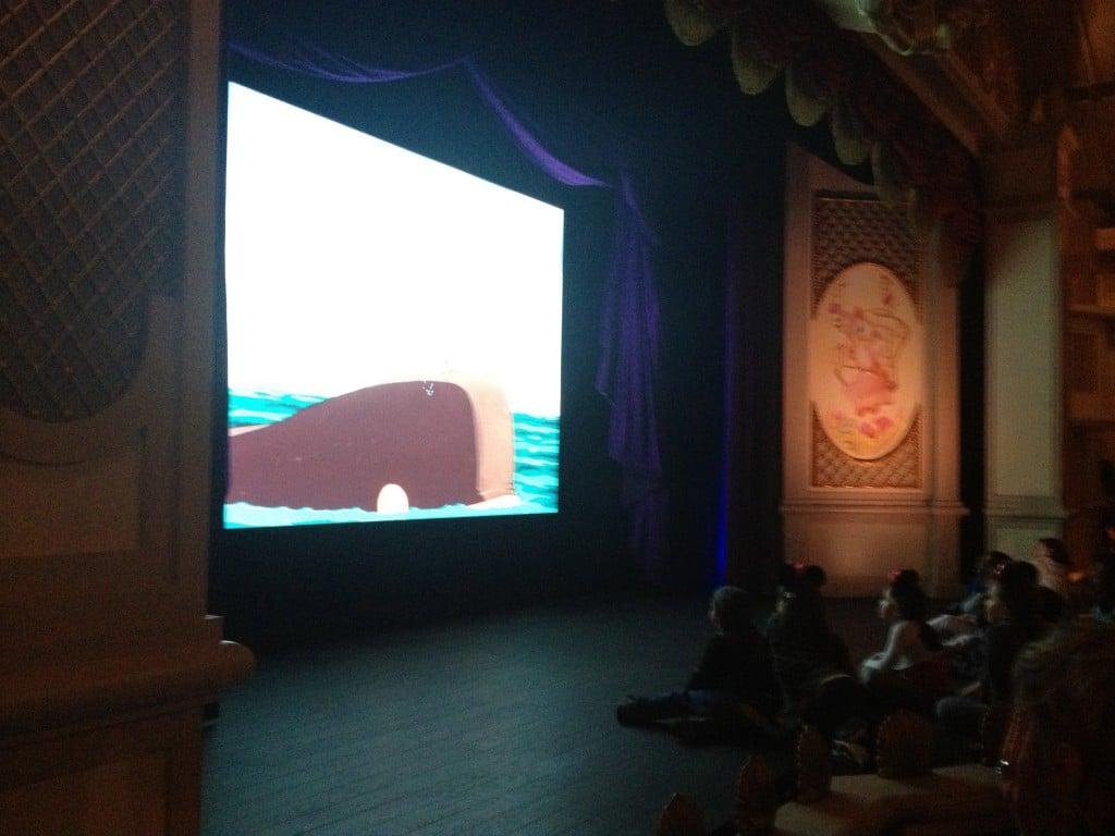 Devant l'écran quelques enfants sont assis. Meet Mickey.